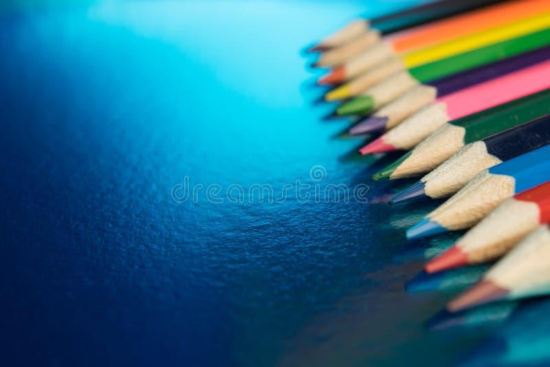 Μπλε υπόβαθρο με τα χρωματισμένα μολύβια στοκ εικόνες