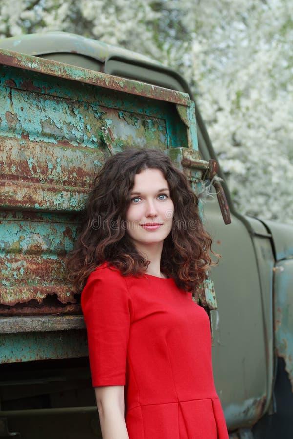 Μπλε-eyed brunette που στέκεται στο παλαιό σώμα φορτηγών και το ανθίζοντας υπόβαθρο οπωρωφόρων δέντρων στοκ εικόνες με δικαίωμα ελεύθερης χρήσης