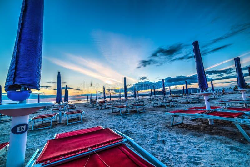 Μπλε parasols θαλασσίως στο ηλιοβασίλεμα στοκ εικόνες