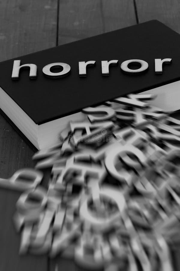 Μυθιστόρημα βιβλίων με τη φρίκη λέξης και τις θολωμένες επιστολές που βγαίνουν από τις σελίδες στοκ φωτογραφία