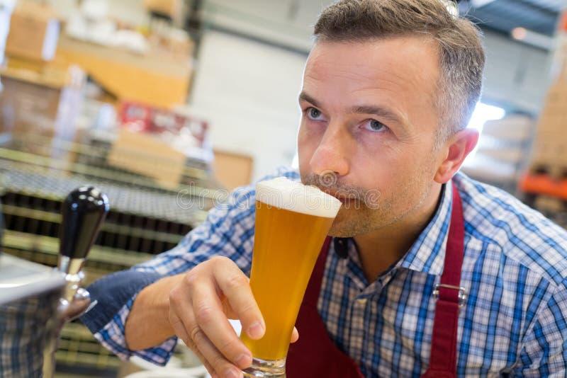 Μυρίζοντας μπύρα ζυθοποιών κινηματογραφήσεων σε πρώτο πλάνο στο εργοστάσιο ζυθοποιείων στοκ φωτογραφία με δικαίωμα ελεύθερης χρήσης