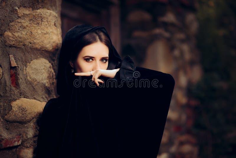 Μυστήρια μελαχροινή μάγισσα στο μαύρο με κουκούλα ακρωτήριο στοκ φωτογραφίες