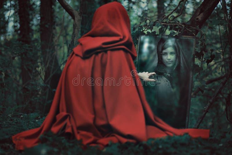 Μυστήρια με κουκούλα γυναίκα μπροστά από έναν μαγικό καθρέφτη στοκ εικόνες