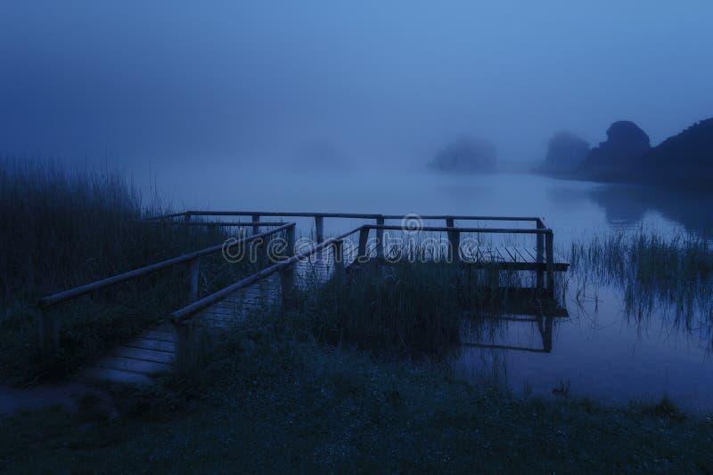 Μυστήριος ξύλινος λιμενοβραχίονας στη λίμνη τη νύχτα στοκ εικόνα