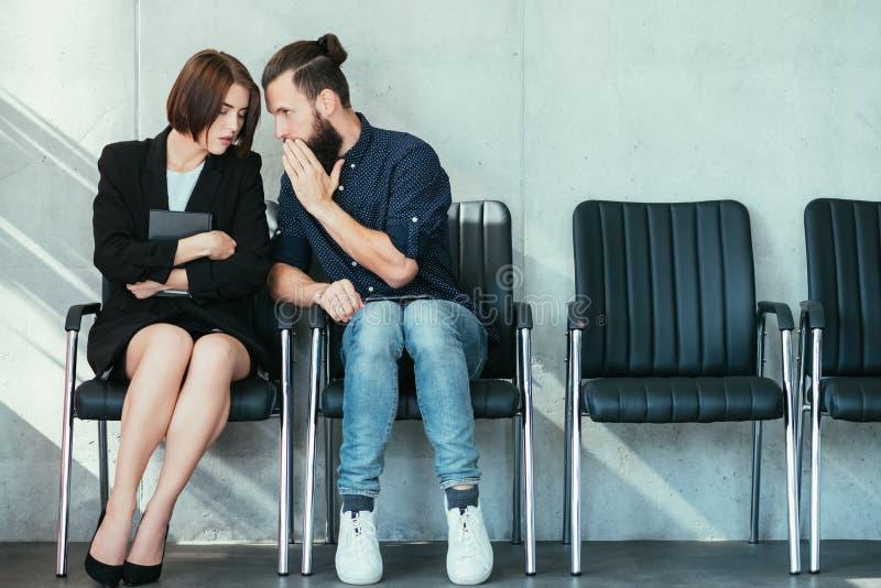 Μυστικά κουτσομπολιού γραφείων αυτιών γυναικών ψιθυρίσματος ανδρών στοκ φωτογραφία