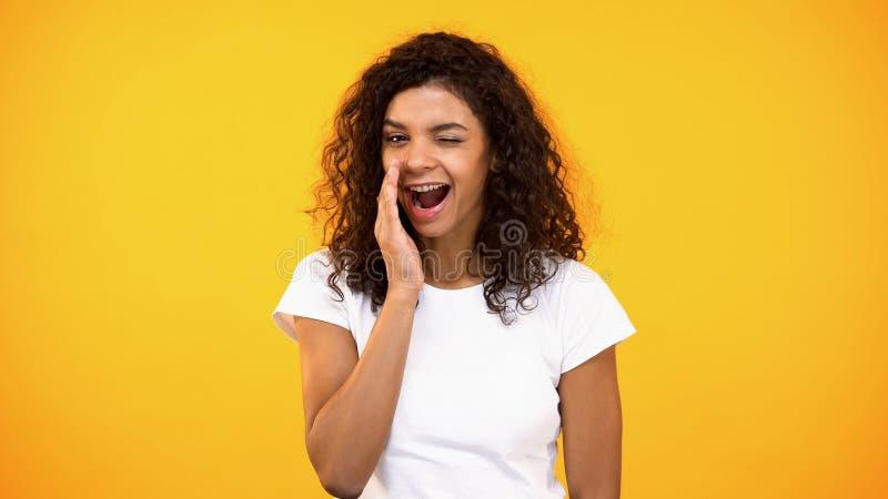 Μυστικά ψιθυρίσματος γυναικών χαμόγελου και κλείσιμο του ματιού στο κίτρινο υπόβαθρο καμερών, φήμες στοκ φωτογραφία με δικαίωμα ελεύθερης χρήσης