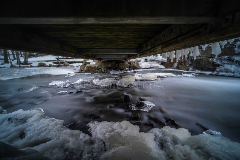 Μυστική εικόνα του νερού που ρέει κάτω από τη μικρή γέφυρα με τον πάγο και το κρύο καιρό στοκ φωτογραφίες