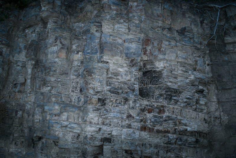 Μυστικός βαλμένος σε στρώσεις γκρίζος-μπλε τοίχος βράχου Grunge με την ανώμαλη επιφάνεια στοκ εικόνες