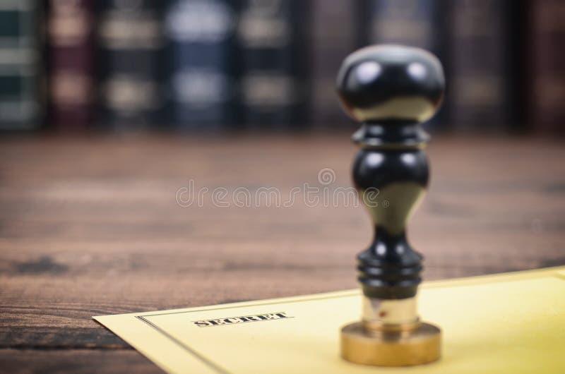 Μυστικός τύπος σφραγίδων εγγράφων και συμβολαιογράφων στο ξύλινο υπόβαθρο στοκ φωτογραφία