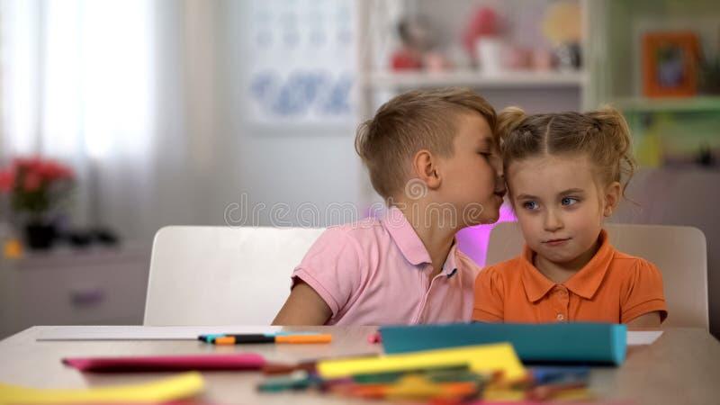 Μυστικό ψιθυρίσματος αδελφών στο αυτί αδελφών, επικοινωνία παιδιών, κουτσομπολιό στοκ φωτογραφίες με δικαίωμα ελεύθερης χρήσης