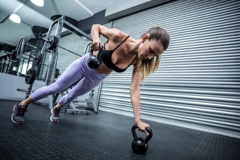 Μυϊκή γυναίκα που κάνει pushups με τα kettlebells στοκ εικόνες