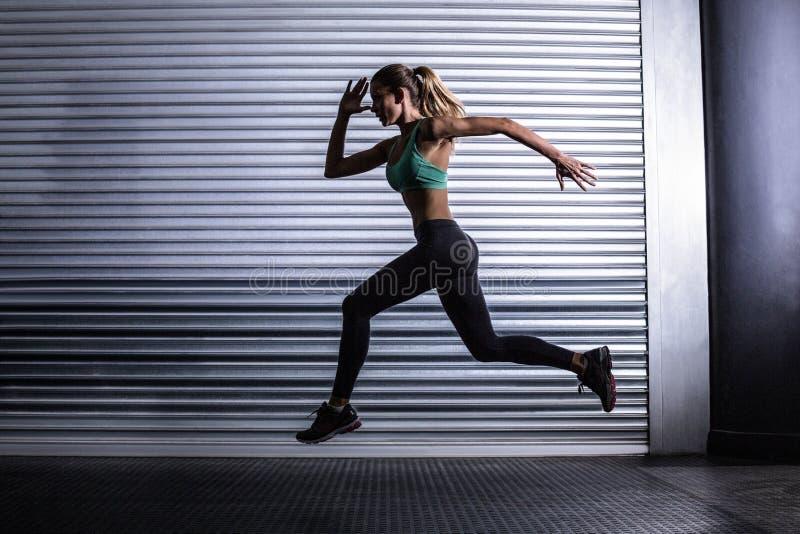 Μυϊκή γυναίκα που τρέχει στο δωμάτιο άσκησης στοκ φωτογραφία
