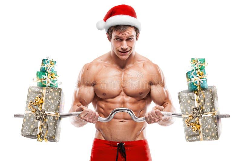 Μυϊκός Άγιος Βασίλης που κάνει τις ασκήσεις με τα δώρα πέρα από το άσπρο backg στοκ φωτογραφία με δικαίωμα ελεύθερης χρήσης