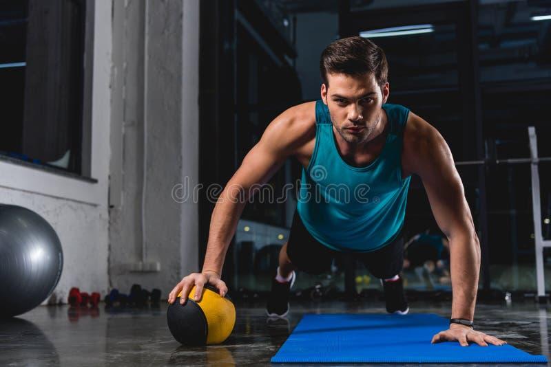 μυϊκός αθλητικός τύπος που κάνει την ώθηση UPS με τη σφαίρα ιατρικής στο χαλί γιόγκας στοκ φωτογραφία