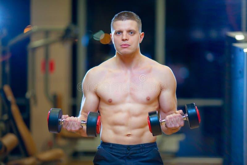Μυϊκός νεαρός άνδρας που κάνει τη βαρέων βαρών άσκηση για τους δικέφαλους μυς με τους αλτήρες στη σύγχρονη κεντρική γυμναστική ικ στοκ εικόνες