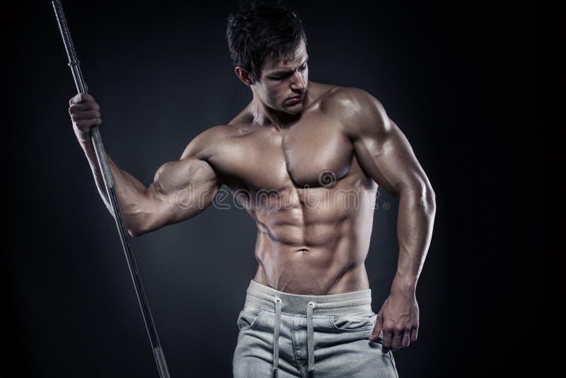 Μυϊκός τύπος bodybuilder που κάνει την τοποθέτηση με τους αλτήρες στοκ φωτογραφίες