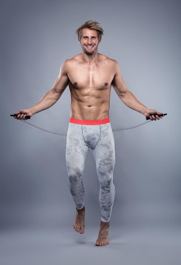 Μυϊκός τύπος bodybuilder που κάνει τις ασκήσεις με το σχοινί άλματος στοκ εικόνες με δικαίωμα ελεύθερης χρήσης