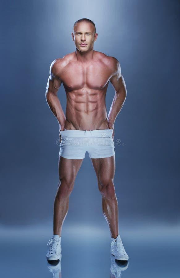 Μυϊκό άτομο γυμνοστήθων που στέκεται στο γκρίζο υπόβαθρο στοκ φωτογραφίες