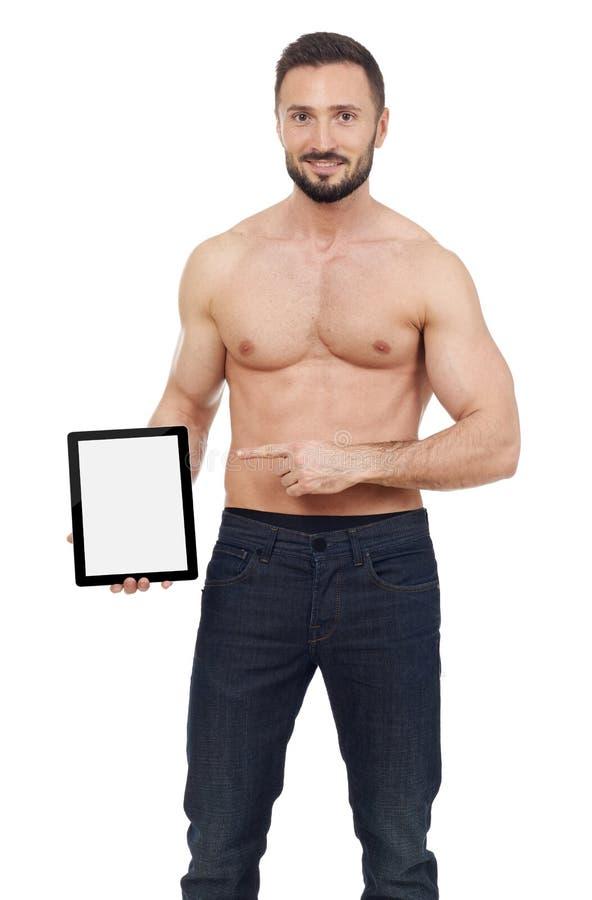 Μυϊκό άτομο που δείχνει μια ψηφιακή ταμπλέτα στοκ εικόνες