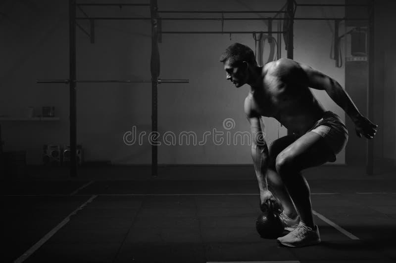 Μυϊκό άτομο που επιλύει με το kettlebell στη γυμναστική στοκ εικόνα με δικαίωμα ελεύθερης χρήσης
