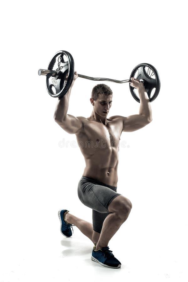 Μυϊκό άτομο που στέκεται στο γόνατο, που κρατά barbell πέρα από το κεφάλι του στοκ εικόνα με δικαίωμα ελεύθερης χρήσης