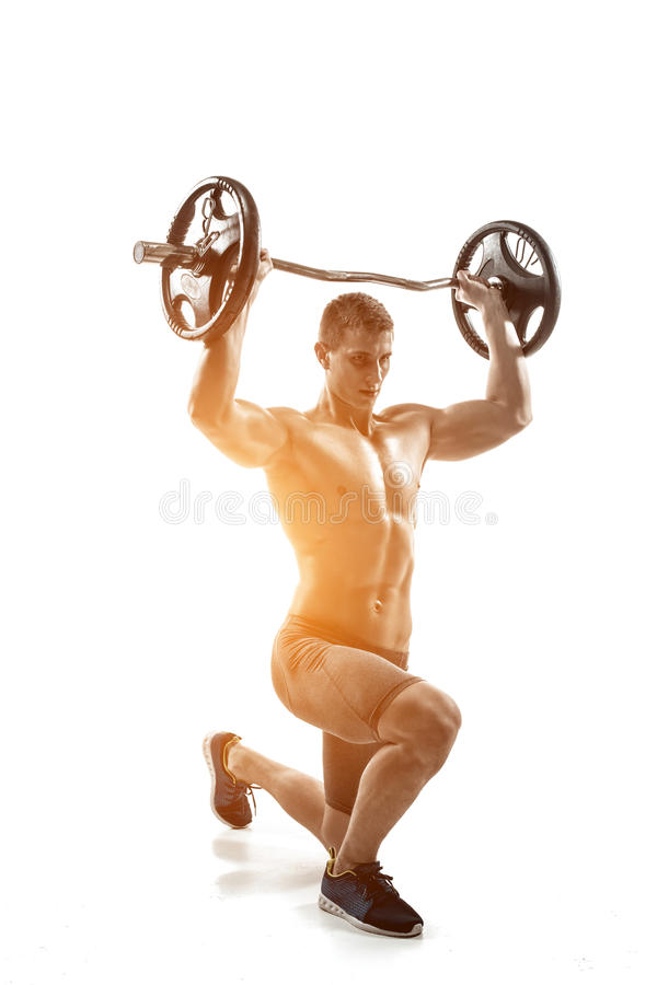 Μυϊκό άτομο που στέκεται στο γόνατο, που κρατά barbell πέρα από το κεφάλι του στοκ φωτογραφίες με δικαίωμα ελεύθερης χρήσης