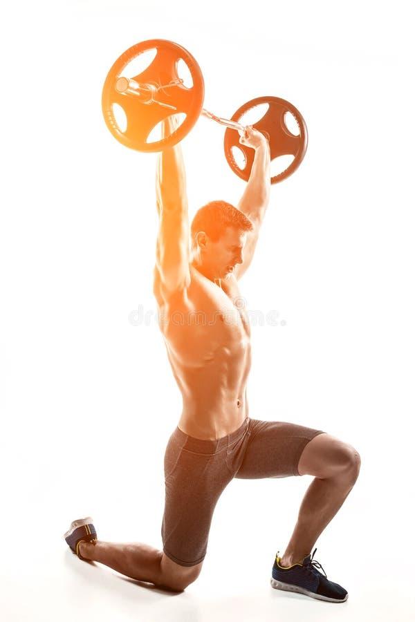 Μυϊκό άτομο που στέκεται στο γόνατο, που κρατά barbell πέρα από το κεφάλι του στοκ εικόνα