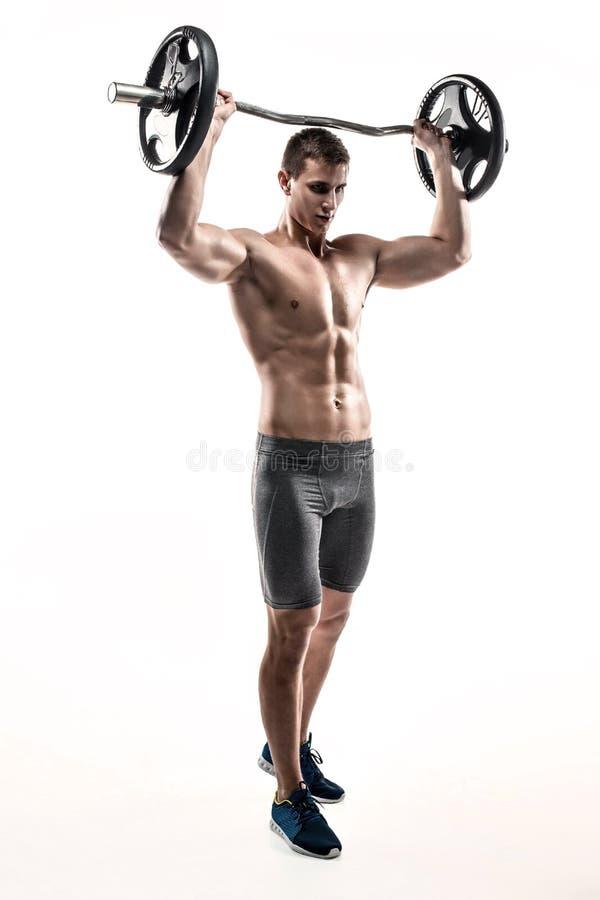 Μυϊκό άτομο που στέκεται στο γόνατο, που κρατά barbell πέρα από το κεφάλι του στοκ φωτογραφία με δικαίωμα ελεύθερης χρήσης