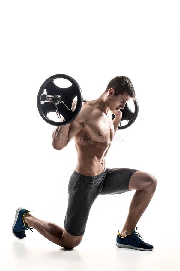 Μυϊκό άτομο που στέκεται στο γόνατο, που κρατά barbell πέρα από το κεφάλι του στοκ φωτογραφία