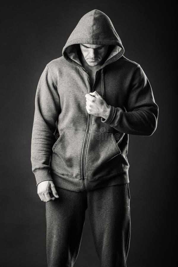 Μυϊκό άτομο σε ένα αθλητικό σακάκι σε ένα σκοτεινό υπόβαθρο στοκ φωτογραφία με δικαίωμα ελεύθερης χρήσης