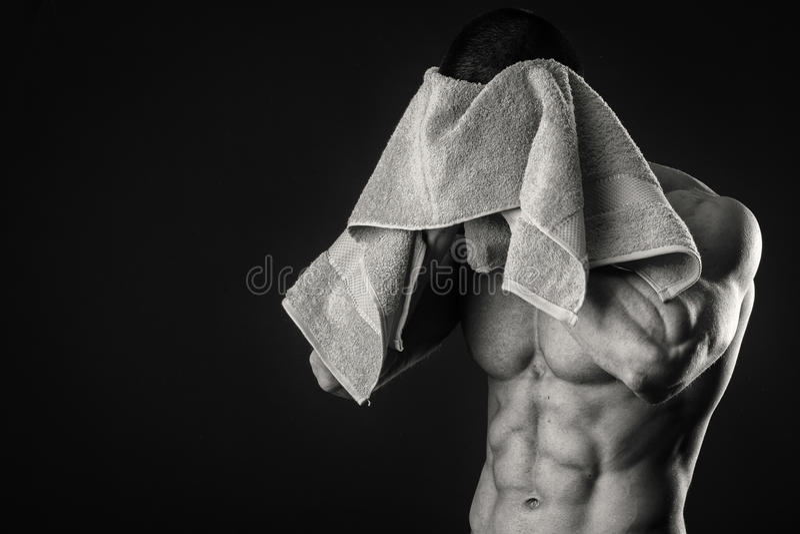 Μυϊκό άτομο σε ένα σκοτεινό υπόβαθρο στοκ εικόνες