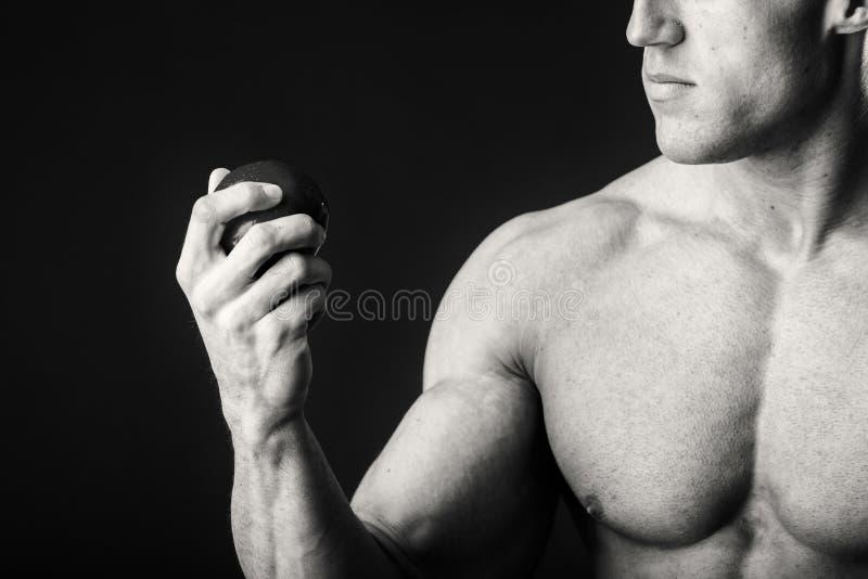 Μυϊκό άτομο σε ένα σκοτεινό υπόβαθρο στοκ εικόνα με δικαίωμα ελεύθερης χρήσης