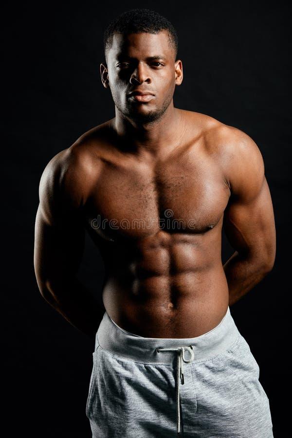 Μυϊκό σοβαρό bodybuilder με τα χέρια στην πλάτη του που εξετάζει τη κάμερα στοκ εικόνα
