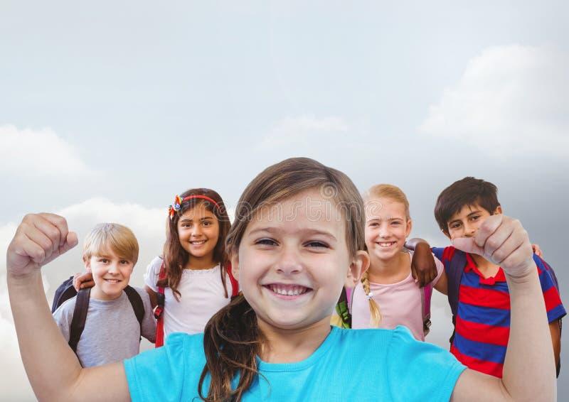 Μυ'ες κάμψης κοριτσιών με τους φίλους μπροστά από το γκρίζο υπόβαθρο στοκ φωτογραφία