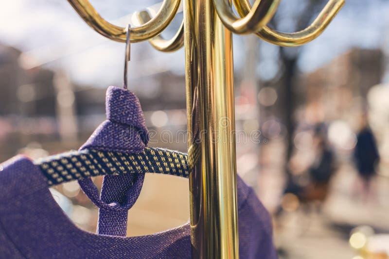 Μωβ φόρεμα κρεμασμένο σε χρυσό ράφι ρούχων στοκ εικόνα με δικαίωμα ελεύθερης χρήσης
