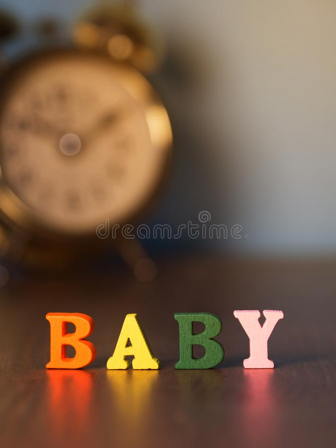 Μωρό Αγγλικό αλφάβητο φιαγμένο από ξύλινο χρώμα επιστολών Μωρό αλφάβητου στον ξύλινο πίνακα και το εκλεκτής ποιότητας ξυπνητήρι στοκ εικόνες