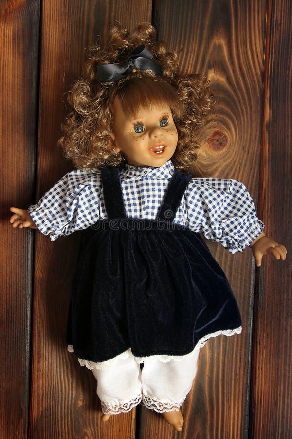 Μωρό - κούκλα στο ξύλινο υπόβαθρο στοκ φωτογραφίες