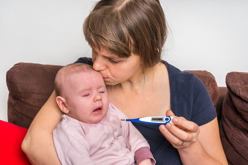 Μωρό νηπίων με τον πυρετό και ανησυχημένη μητέρα με το θερμόμετρο στοκ εικόνες με δικαίωμα ελεύθερης χρήσης