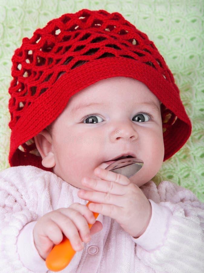 Μωρό πορτρέτου στο κόκκινο καπό στοκ εικόνες