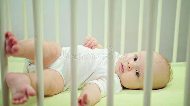 Μωρό που βρίσκεται σε ένα παχνί στο σπίτι και που παίζει στοκ εικόνες με δικαίωμα ελεύθερης χρήσης