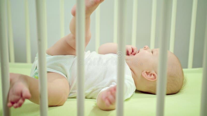 Μωρό που βρίσκεται σε ένα παχνί που τρώει στο σπίτι τα δάχτυλά του στοκ εικόνα με δικαίωμα ελεύθερης χρήσης