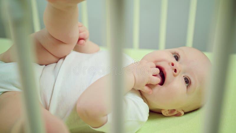 Μωρό που βρίσκεται σε ένα παχνί που τρώει τα δάχτυλά του στοκ φωτογραφία