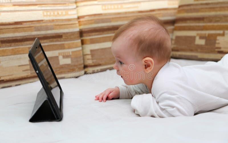 Μωρό που εξετάζει ένα νέο PC ταμπλετών στοκ εικόνα