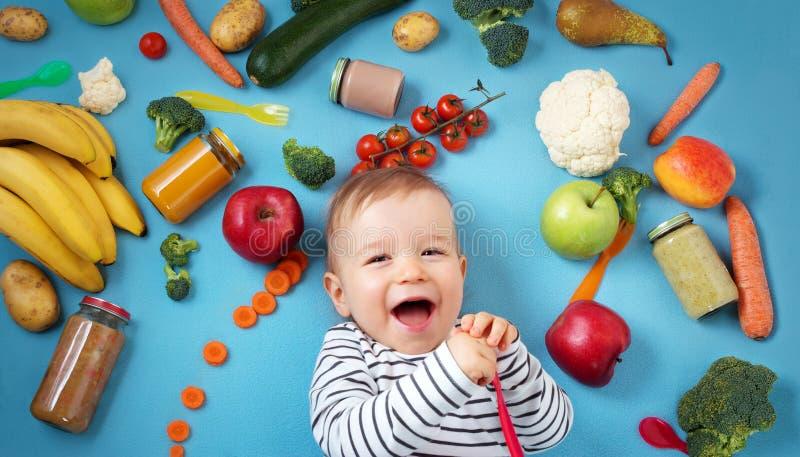 Μωρό που περιβάλλεται με τα φρούτα και λαχανικά στοκ φωτογραφία