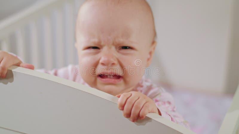 Μωρό που στέκεται σε ένα παχνί στο σπίτι crying στοκ εικόνα με δικαίωμα ελεύθερης χρήσης