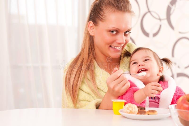 μωρό που ταΐζει τις νεολαίες γυναικών πορτρέτου της στοκ φωτογραφία με δικαίωμα ελεύθερης χρήσης