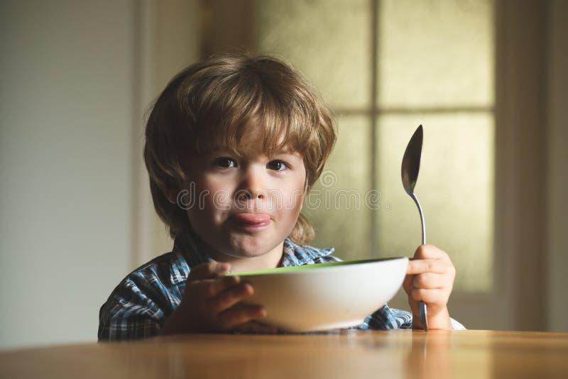 Μωρό που τρώει τα τρόφιμα στην κουζίνα Το χαριτωμένο παιδί τρώει Συνεδρίαση αγοράκι παιδιών γέλιου χαριτωμένη στο highchair και κ στοκ εικόνες