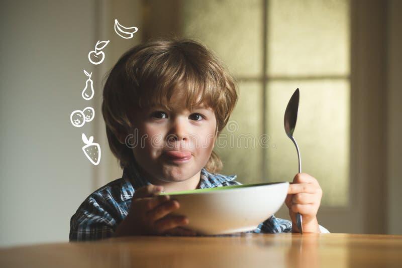 Μωρό που τρώει τα τρόφιμα στην κουζίνα Το χαριτωμένο παιδί τρώει Συνεδρίαση αγοράκι παιδιών γέλιου χαριτωμένη στο highchair και κ στοκ εικόνες με δικαίωμα ελεύθερης χρήσης
