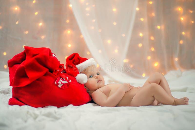 Μωρό σε ένα καπέλο Χριστουγέννων με την κόκκινη τσάντα Άγιου Βασίλη στοκ φωτογραφία με δικαίωμα ελεύθερης χρήσης
