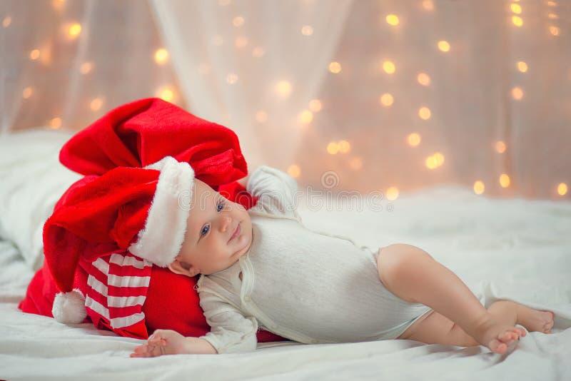Μωρό σε ένα καπέλο Χριστουγέννων με την κόκκινη τσάντα Άγιου Βασίλη στοκ εικόνα με δικαίωμα ελεύθερης χρήσης